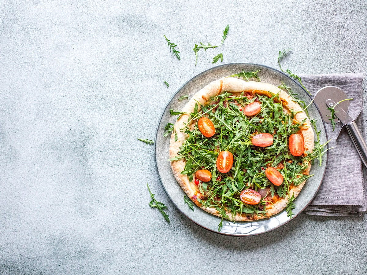 Pizza with tomatoes on a plate. Placed on a grey concrete background